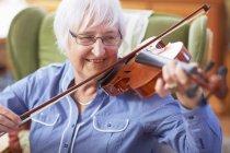 Donna anziana a casa a suonare il violino — Foto stock