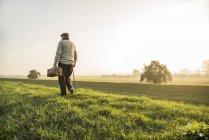 Homem sênior com saco andando na paisagem rural — Fotografia de Stock