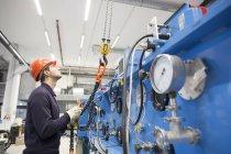 Giovane tecnico che prende il gancio di un derrick nella sala industriale — Foto stock