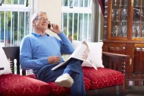 Senior man on the phone reading newspaper at home — Stock Photo
