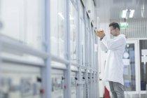 Chimico che tiene fiaschetta fondo rotondo in laboratorio — Foto stock