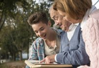 Senior man with grandson and daughter looking at photo album — Stock Photo