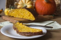 Slice of pumpkin bread on a dish and pumpkins in the background — Stock Photo