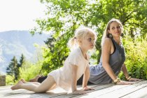 Mother and daughter practicing yoga on wooden terrace — Stock Photo