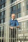 Homme d'affaires avec tablette numérique et écouteurs à l'extérieur de l'immeuble de bureaux — Photo de stock