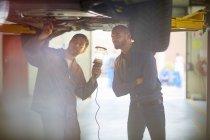 Car mechanics in repair garage looking at car bottom — Stock Photo