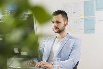 Giovane uomo d'affari in ufficio a lavorare al computer — Foto stock