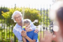 Grandson and grandmother splashing at grandfather with water gun — Stock Photo