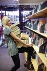 Estudiante que lleva un montón de libros en una biblioteca - foto de stock