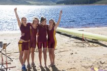 Four female rowers cheering at lakeshore — Stock Photo