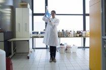 Молодий вчений жінка з стоячи лампа скла в хімічної лабораторії — стокове фото
