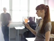Woman in office looking at cell phone — Stock Photo