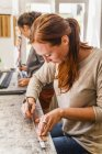 Woman cutting elastic fabric rubber band in saddlery — Stock Photo