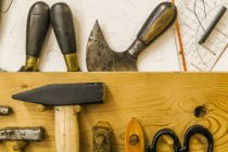 Saddler's tools on tool board over white surface — Stock Photo