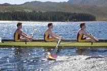 Barca di rematura di uomini in lago con le montagne su priorità bassa — Foto stock