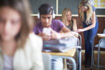 Cropped portrait of teenage students in classroom — Stock Photo