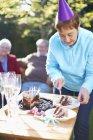Senior woman on a birthday garden party — Stock Photo
