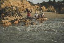 Three teenagers sitting on beach at sunset — Stock Photo