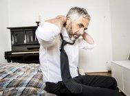 Businessman binding tie in his bedroom — Stock Photo
