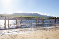 Гребцов, перевозящих лодки в воду возле Песчаный пляж — стоковое фото