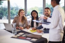 Waiter bringing water to business people working at a restaurant — Stock Photo