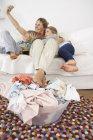 Mère, fille et fils sur canapé prenant un selfie avec panier à linge étage — Photo de stock