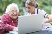 Enfermeira e senior mulher usando laptop juntos — Fotografia de Stock