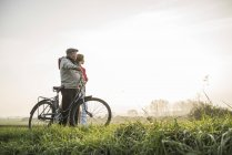 Senior man and daughter in rural landscape with bicycle — Stock Photo