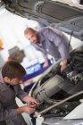 Two car mechanics at work in repair garage — Stock Photo