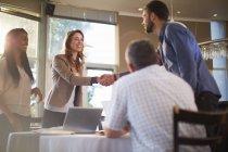Zwei Personen, die sich bei einem Geschäftstreffen in einem Restaurant begrüßen — Stockfoto