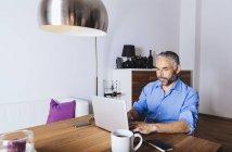 Hombre de negocios trabajando con el portátil en casa oficina - foto de stock