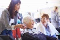 Female hairdresser cutting hair of senior woman — Stock Photo