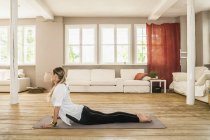 Woman practicing yoga in living room — Stock Photo