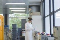 Wissenschaftlerin steht mit Liste in Chemielabor — Stockfoto