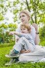 Мать и маленький сын сидят вместе на лугу и смотрят что-то — стоковое фото