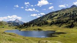 Lago e montanha Kalbelesee azul céu nublado de dia, Vorarlberg, Áustria, — Fotografia de Stock