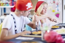 Children dressed up as pirates on a party sitting at table eating pizza — Stock Photo