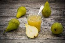 Marmellata di pere biologiche intere ed affettate e vetro di pera su legno grigio — Foto stock