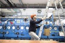 Un jeune technicien monte une échelle dans un hall industriel — Photo de stock