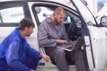 Two car mechanics with laptop in repair garage — Stock Photo