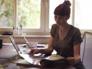 Frau am Schreibtisch mit Laptop-Lesemagazin — Stockfoto