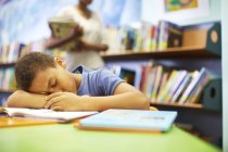 Sleeping boy in library sleeping at the table — Stock Photo