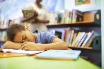Garçon endormi dans la bibliothèque de dormir à la table — Photo de stock