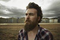 Серьезный человек с бородой в заброшенном месте — стоковое фото