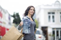 Woman with shopping bag walking on the street — Stock Photo