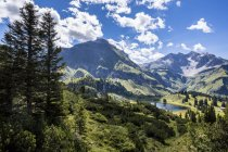 Austria, Vorarlberg, mountainscape and Koerbersee with peaks under clouds — Stock Photo