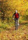 Homme à vélo de montagne dans la forêt automnale — Photo de stock