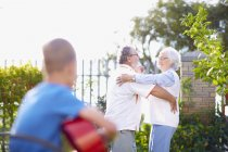 Senior couple dancing in park with grandson playing guitar — Stock Photo