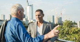 Dos hombres de negocios de pie en el puente y hablar - foto de stock