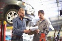 Kfz-Mechaniker mit Kunden in Werkstatt — Stockfoto